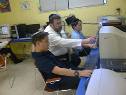 Rabbi Bukspan teaches PowerPoint to boys in computer class.