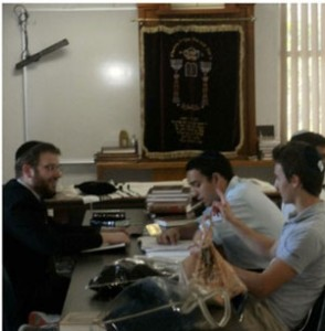 Rabbi Josh Musicant works with Eliezer Barman and Shmuel Zidel (pointing) during a Project Hemshech study period.