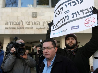 Chairman of Histadrut Labor Federation,Ofir Eini stands with protesters as they hold banners and chant slogans during a demonstration against the current employment status of contract workers, at the entrance to the National Labor Court in Jerusalem, on Jan 09, 2012, prior to a hearing on the request by the Histadrut Labor Federation to hold a general strike on the issue of contract labor. No agreement has been reached between the union and the treasury, the Center for Local Government and employers.
