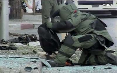 A police bomb squad officer checks a bag at the scene of the bombing