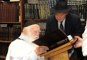 Rabbi Chaim Kanievsky, admires HaMafteach as author Daniel Retter looks on.