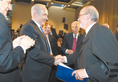 Judge Asher Grunis, new president of Israel's Supreme Court, is congradulated by Prime Minister Netanyahu at inauguration ceremony on Tuesday.
