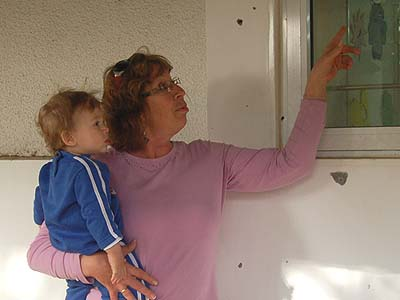 Carol Simantov (with friend) pointing at a shrapnel crack in a kindergarten window.
