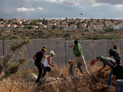 Palestinians hurl stones onto the Israeli side of the separation barrier