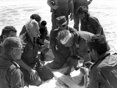 Former chief of staff Haim Bar Lev consults with Major General Ariel Sharon and Moshe Dayan during the Yom Kippur War.