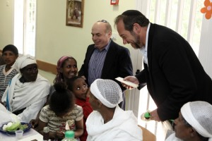 "Rabbi Yechiel Eckstein, founder and president of the International Fellowship of Christians and Jews (IFCJ) (R),and Head of the Jewish Agency, Natan Sharansky stand with newly arrived Jewish immigrants from Ethiopia as they attend a rehersal of a Passover holiday dinner (known as a ""seder""), organized by the Jewish Agency and IFCJ at an immigrant's centre in Mevasseret Zion, near Jerusalem April 02, 2012."