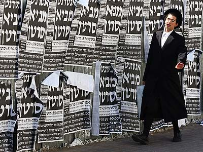 An Ultra Orthodox Jewish youth walking past signs warning that the Internet causes cancer.