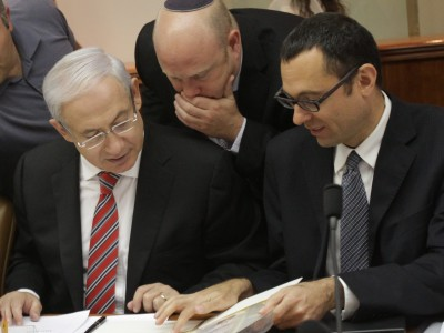 Israel's Prime Minister Benjamin Netanyahu speaks with his bureau chief Gili Sheffer (L) and cabinet secretary Tzvika Hauser (R) at the weekly cabinet meeting.