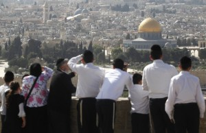 Jews stand in Mount of Olives over looking towards the walls of the Old City of Jerusalem and gaze towards the Temple Mount, where two temples stood and were destroyed. Jews pray for the reestablishment of a third temple in the same place.