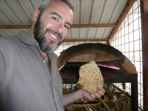 Yishai Fleisher shows off a Matzah after manning the oven of a Matzah bakery in Beit El, Israel