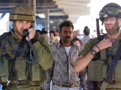 A Palestinian man walking behind two IDF soldiers at a crossing.