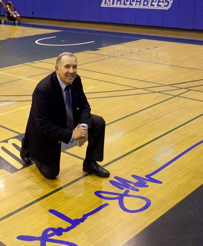 Coach Halpert poses with his signature at Yeshiva University's Max stern Athletic Center.