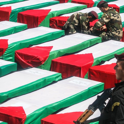 Palestinian security personnel overseeing the transfer of the remains of dozens of Palestinian terrorists.