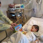 Young volunteer from Philadelphia presents gift to child at Beth Israel Hospital in Manhattan.