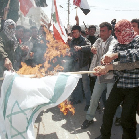 Palestinians burn an Israeli flag