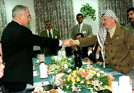 Netanyahu and Arafat shaking hands at the conclusion of the Hebron Agreement.