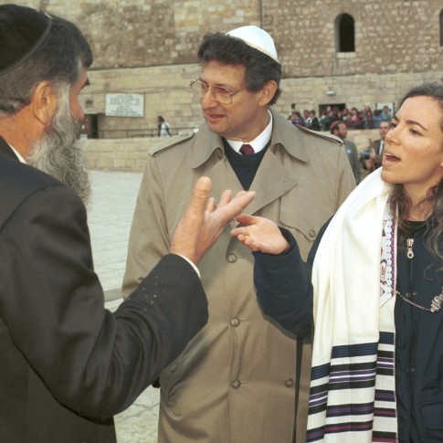 An orthodox Jewish man argues with a reform Jewish woman wearing a prayer shawl at the Western Wall.
