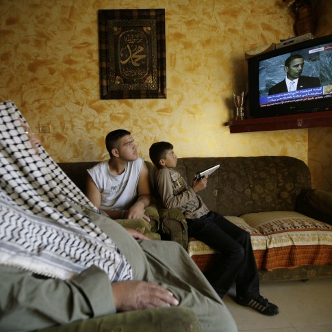 An arab family watching President Obama speak on TV