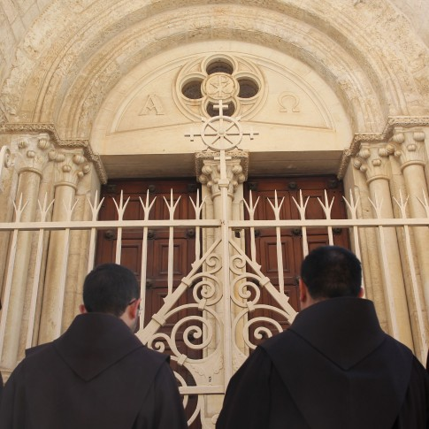 Monks at an entrance to the Church of the Redeemer in Jerusalem