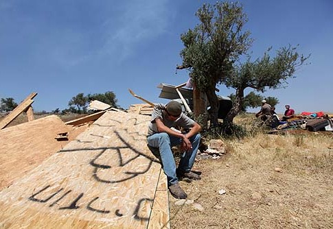 A settler sits on a wooden wall after Security forces demolished structures at the Ramat Migron outpost.