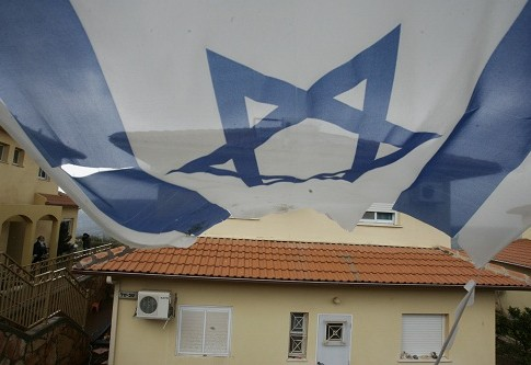 An Israeli flag drapes a house in Bruchin, the newest settlement in Samaria.