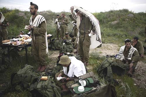 Haredi soldiers praying in the fields. Some are less welcome in their own shuls.