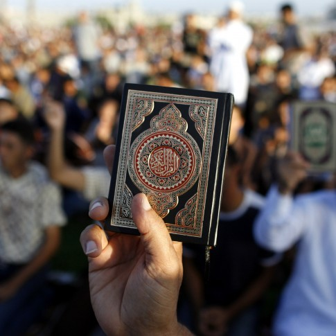Palestinian men hold up the Quran