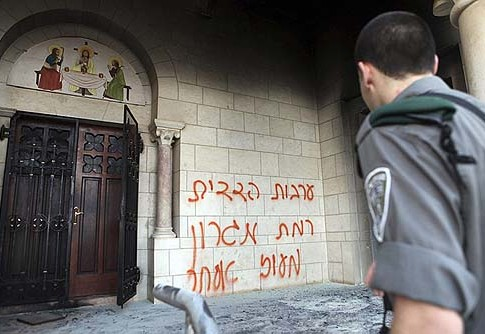 An Israeli policeman inspects the graffiti sprayed on the wall of the monastery in Latrun, Sept. 4 2012.
