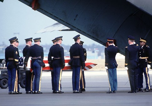 U.S. Army pallbearers prepare to carry the transfer case of a deceased U.S. soldier into an aircraft during a departure ceremony on the flight line.