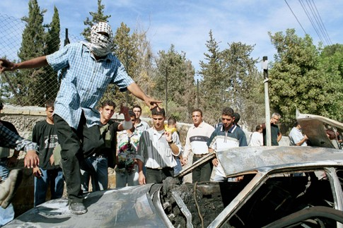 A Palestinian celebrates on top of the burned car of the two Israeli soldiers who were taken from it and lynched next to Ramallah, October 12, 2000.