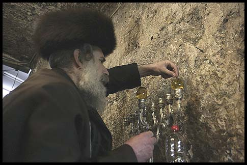 Lighting a menorah in the tomb of Rabbi Shimon Hazadik
