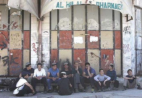Jewish youths sitting near the Mechpela House, whose legal Jewish owners are barred from residing.
