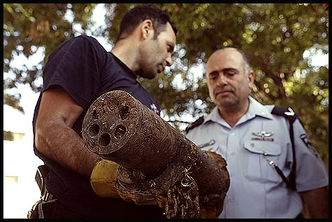 An Israeli policeman examines a Kassam rocket that was fired by Arab terrorists from Gaza and landed in the southern town of Sderot.