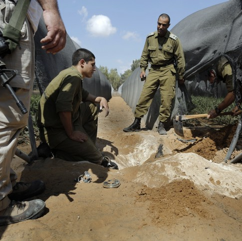 Israeli army soldiers from the bomb squad search for a mortar shell fired from Gaza.