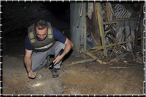 Israeli Police sapper inspecting a mortar shell fired from Gaza Strip in Eshkol Regional Council earlier this year.