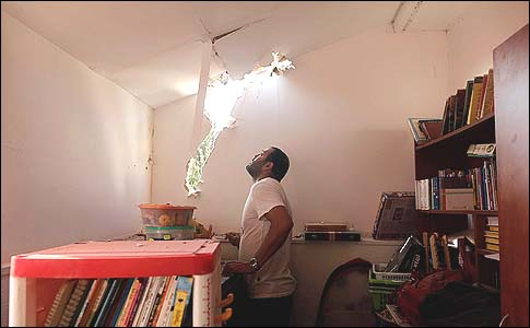 A resident of Sderot examines the damage to his home after a Kassam rocket fired by Arab terrorists in Gaza landed in his living room.