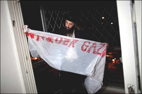 "A Haredi man hangs a sign calling to ""Conquer Gaza"" in his apartment building in Kiryat Malachi which was struck by a grad rocket fired from Gaza killing 3."