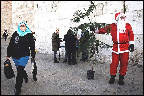An Arab dressed as Santa Claus handing out Christmas trees donated by the Jerusalem municipality near the Old City wall.