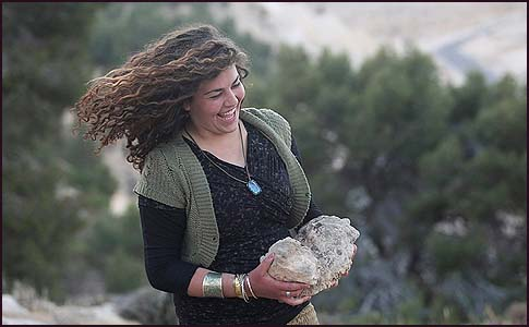 An Israeli activist building a stone wall on a hill in the area known as E1, opposite the Jewish town of Maale Adumim.