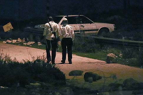 Armed Jews walk on the road leading to the outpost of Oz Zion, December 28, 2012.