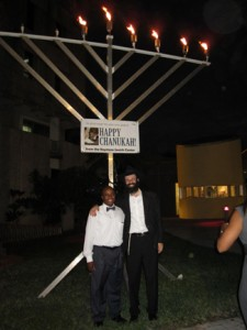 Rabbi Daniel Green (right) of the Keystone Jewish Center poses with North Miami Mayor Andre Pierre in front of an 18-foot-menorah at North Miami City Hall.