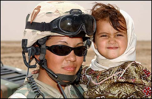 Army Spc. Janie Reyna, a member of the 56th Brigade Combat Team, 36th Infantry Division, Texas Army National Guard, holds an Iraqi child she befriended during a civil affairs mission in southern Iraq.
