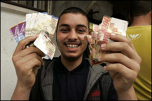 A Palestinian showing the money he withdrew from an ATM in Rafah in the southern Gaza Strip.