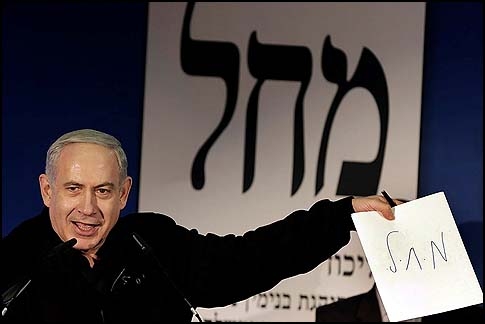 Prime MInister Benjamin Netanyahu in an appearance in Ashdod, holding up a paper with the joint Likud-Yisrael Beitenu election ticket.