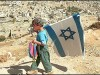 A Jewish boy wearing a kippa and holding an Israeli flag in Hebron.