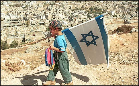 A Jewish boy wearing a kippa and holding an Israeli flag in Hebron.