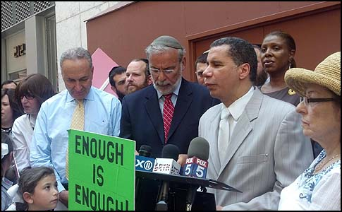 "Assemblyman Dov Hikind wrote on his Facebook page below this image: ""The sign says it all: Enough Is Enough."" To Hikind's left stands U.S. Senator Chuck Schumer, to his left former NY Governor David Paterson. They spoke up for the release of businessman Jacob Ostreicher from Bolivian jail (he was, last December)."