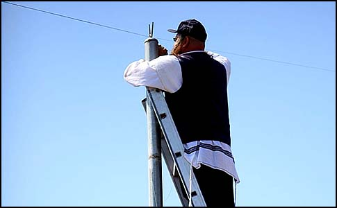 A man standing on a ladder to hang an eruv wire around the Gilo neighborhood in south Jerusalem.
