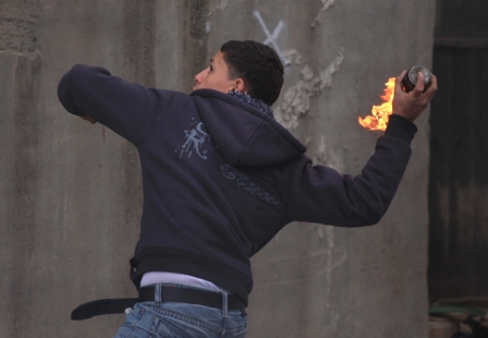 A Palestinian Authority Arab prepares to hurl firebomb at Israeli soldiers .