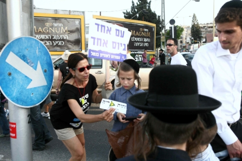"A Secular woman handing a Hareidi child a ""Universal Draft"" sticker during a protest."